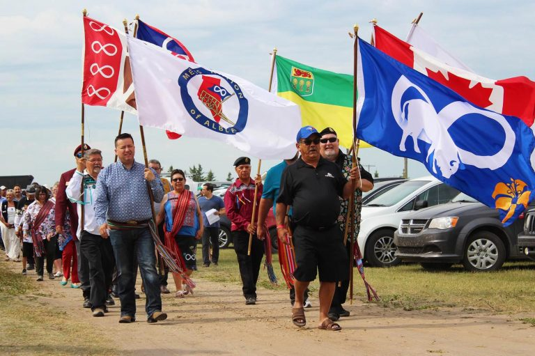 Procession walking with flags at Back to Batoche 2018